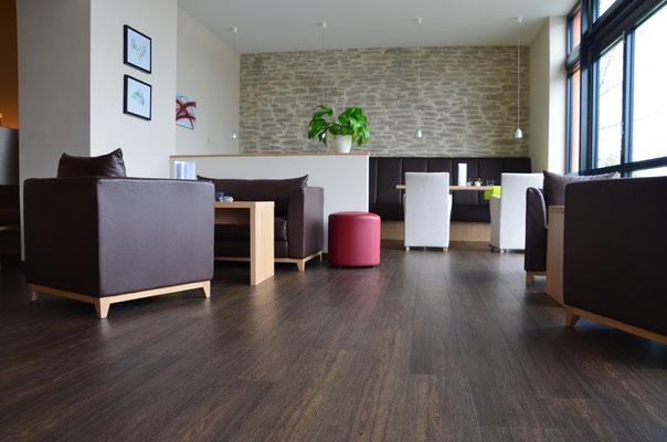 Lounge im Hotel Surendorff mit PVC-Plankenbelag in dunklem Design - geeignet für gewerbliche Objekte