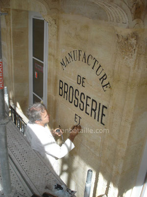 Reproduction du nom de la boutique sur mur en pierre