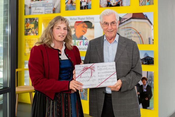 """Musikverein Langenneufnach e.V.: Roswitha Haas (2. Vorstand Musikverein Langenneufnach e.V.) übergab ein Geschenkpaket mit 300 Euro an Michael Wagner für seine Stiftung  """"Kinderlachen""""."""