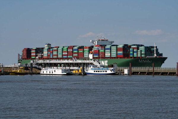 """Blick auf die """"Alte Liebe"""" mit vorbeiziehendem Containerschiff"""