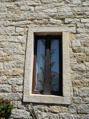 Nicht alle Fenster haben normale Rahmen, nein  - da war ein Schmied am Werk, der seiner Kreativität freien Lauf gelassen hat.