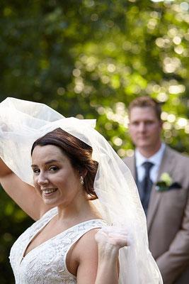 Braut flirtet mit der Kamera, Bräutigam im Hintergrund
