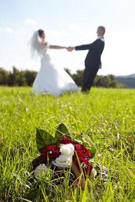 Paar hält sich an den Händen, Blumen im Vordergrund