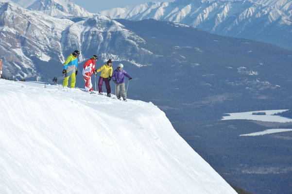Three skiers and a snowboarder looking at a run in Marmot Basin, Jasper National Park © Tourism Jasper