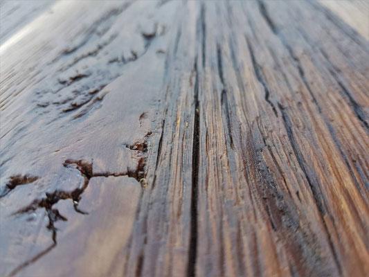 Detailbild Tischplatte aus uraltem Eichenholz mit Rissen und Ästen