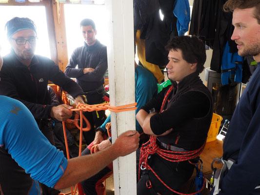 Eric (guide) fait des Travaux Pratiques sur les piliers du refuge.