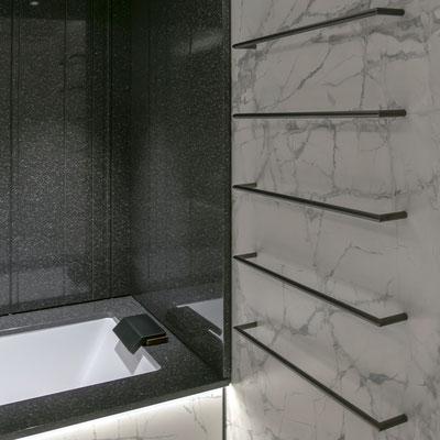 Vonios apdaila - šviesaus keraminio akmens siena ir juodo akrilinio akmens sienelės nuo purslų