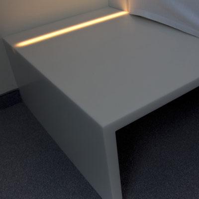 Akrilinio akmens lentyna-spintelė prie lovos su apačioje įmontuota led juosta, kuri išjungus šviesą nematoma / gamintojas: Gforma