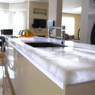 Virtuvės sala su peršviečiamu balto kvarcito stalviršiu ir jame įmontuotomis LED juostomis