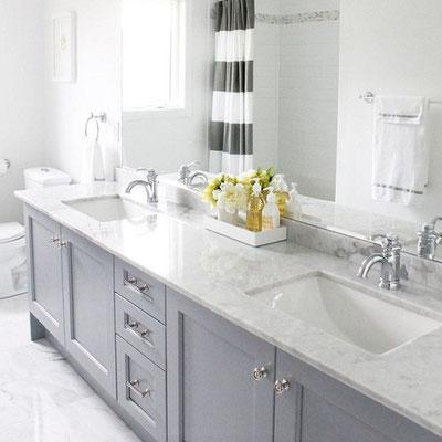Vonios kambario stalviršis iš balto marmuro su sienele ir įmontuotais keraminiais praustuvais