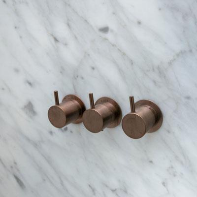 Marmurinėje dušo sienoje įmontuotos čiaupų rankenėlės