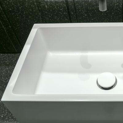 Keturkampis vonios praustuvas iš balto akrilinio akmens pastatytas ant juodo akrilinio akmens spintelės