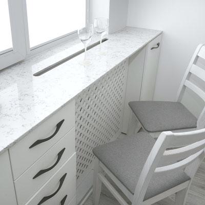 Kvarcinio akmens palangė-baras virtuvėje su išpjova virš radiatoriaus šiltam orui cirkuliuoti