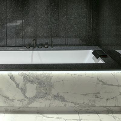 Vonia su balto keraminio akmens apdaila ir juodais akrilinio akmens kraštais bei sienomis