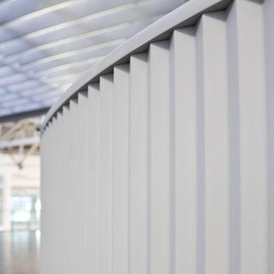 Lenktos formos registratūra iš balto akrilinio akmens verslo centre su grioveliais frezuotu šonu / gamintojas - Gforma
