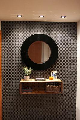 Hall de una clienta decorado con espejo y caja de madera de la tienda