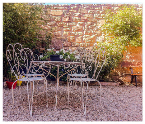 Mesa y sillas antiguas de hierro para disfrutar de este precioso jardín