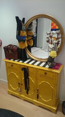 Original aparador amarillo en el recibidor de unos clientes