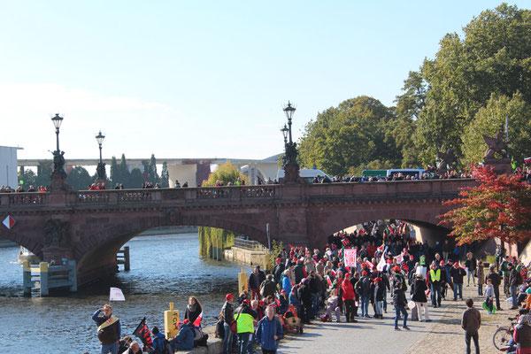 Menschen auf der Brücke und am Spreeufer. Demonstration gegen TTIP am 10.Oktober 2015. Foto: Helga Karl