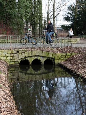 Radfahrer fahren über die Brücke über einem Wassergraben im Volkspark beim Spielplatz. Foto: Helga Karl