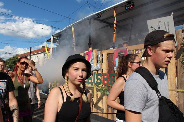 """Jugendliche gehen neben einem Musikwagen im """"Zug der Liebe Berlin  2015"""". Foto: Helga Karl"""