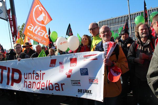 Strahlende Demonstranten mit Transparent mit Logos DGB, SPD, KAB, Linke aus Paderborn. Großdemo gegen TTIP in Berlin. Foto: Helga Karl 10.10.2015