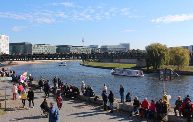 Spreeufer mit Menschen, Blick auf Fernsehturm. Großdemo Stoppt TTIP. Foto: Helga Karl 10.10.2015