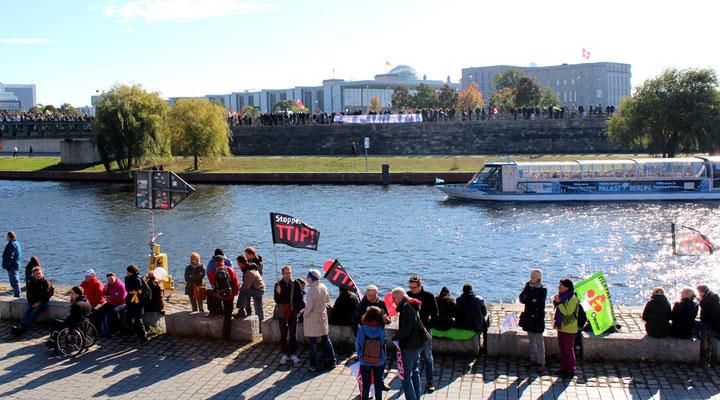 Menschen an beiden Ufern der Spree. Blick auf Reichstag und Parlamentsviertel. Demo Stoppt TTIP. Foto: Helga Karl
