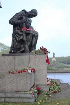 """Skulptur """"Knieender Rotarmist """" mit nieder gelegten Blumen.  9.Mai Sowjetisches Ehrenmal Treptower Park. Foto: Helga Karl"""