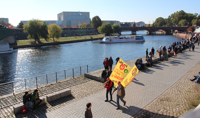 Menschen sammeln sich am Spreeufer und Brücken, Blick auf Kanzleramt. Großdemo Stop TTIP Berlin am 10.10.2015.  Foto: Helga Karl