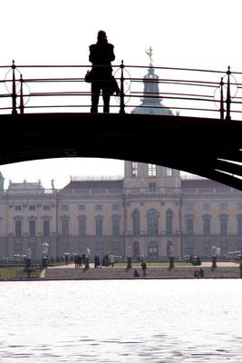 Ein Mensch steht auf der Roten Brücke am Karpfenteich mit Blick auf das Schloss Charlottenburg. Foto: Helga Karl