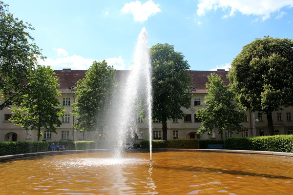 Wasserfontaine vor blühenden Kastanienbäumen und Wohnanlage Ceciliengärten Schöneberg. Foto: Helga Karl