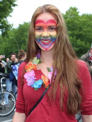 Beim CSD Berlin 2015: Junge Frau mit bemaltem Gesicht in Regenbogenfarben. Foto: Helga Karl