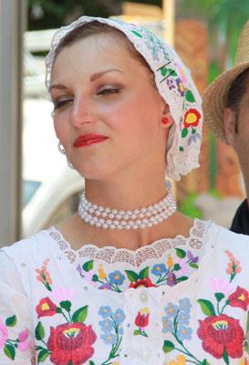 Frau  mit besticktem Kleid und Kopfschmuck. Karneval der Kulturen Berlin. Foto: Helga Karl