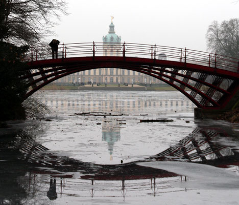 Rote Brücke und Schloss Charlottenburg spiegeln sich im Wasser mit Eisschollen. Foto: Helga Karl