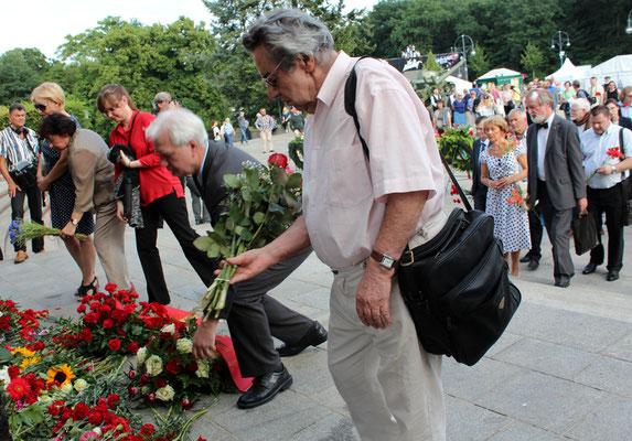 """Menschen legen Blumen nieder, ein Mann mit Roten Rosen, eine Frau mit blauen Kornblumen. Sowjetiwsches Ehrenmal am """"Tag der Trauer"""". Foto: Helga Karl am 22.6.2016"""