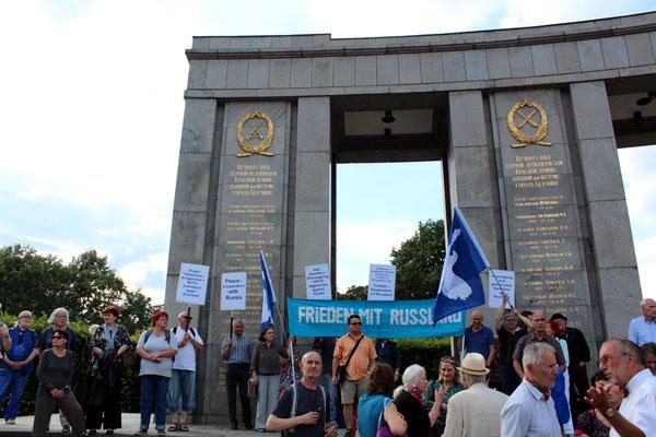"""""""Frieden mit Russland"""" steht auf dem blauen Banner, daneben Fahnen der Friedensbewegung mit Taube. Sowjetisches Ehrenmal Berlin-Tiergarten am Jahrestag des Überfalls von Nazi-Deutschland auf die Sowjetunion.. Foto: Helga Karl 22.6.2016"""