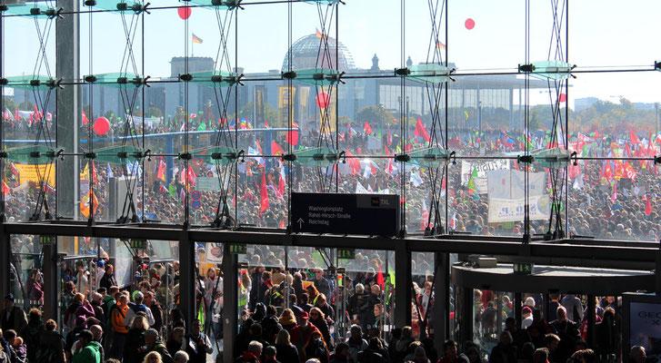 Zehntausende mit Fahnen vor dem Hauptbahnhof, Blick auf Reichstag. Großdemo Stop TTIP Berlin.  Foto: Helga Karl 10.10.2015