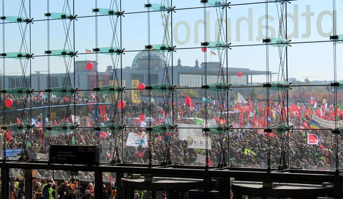 Durch die Glasfront Hauptbahnhof Berlin gesehen: Zehntausende mit bunten roten Fahnen vor Reichstag. Großdemo Stop TTIP Berlin.  Foto: Helga Karl 10.10.2015