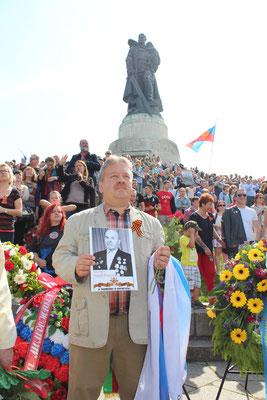 Ein Mann mit russischer Fahne und Foto eines Anhörigen vor dem Hügel mit dem Soldaten mit Kind auf dem Arm. Sowjetisches Ehrenmal Treptow. Foto: Helga Karl am 9. Mai 2015