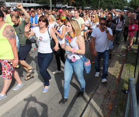 "Menschen tanzen eng gedrängt hinter Musikwagen beim ""Zug der Liebe"". Foto: Helga Karl"