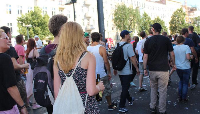 """Blonde Frau mit weißem Rucksackbeutel und weitere Teilnehmer mit Rucksack beim """"Zug der Liebe"""". Foto: Helga Karl"""