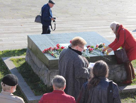 Menschen legen Blumen nieder auf der zerstörten Steinplatte Sowjetisches Ehrenmal Treptow. Foto: Helga Karl am 8.11.2015