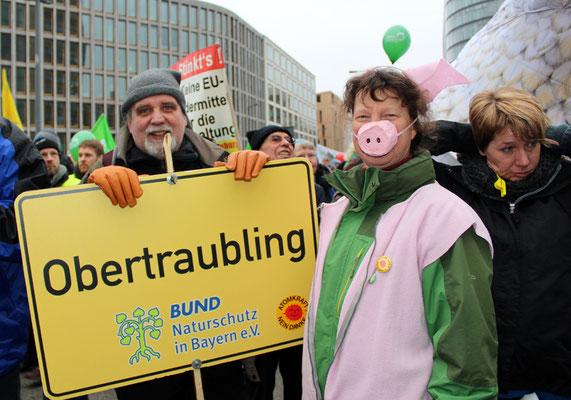 """Mann und Frau mit Schild """"Obertraubling"""" vom Bund Naturschutz in Bayern bei der Demo 2017 in Berlin """"Wir haben es satt"""". Foto: Helga Karl"""