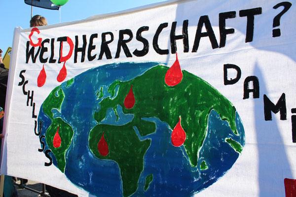 """Plakat """"GWeltDherrschaft ?"""", es tropft Blut. Auf der Großdemo """"Stoppt TTIP"""" in Berlin. Foto: Helga Karl"""