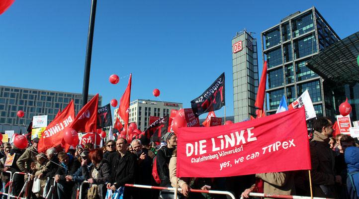 Dicht gedrängte Menschen zwischen Plakaten und Fahnen LINKE. Großdemo Stop TTIP Berlin am 10.10.2015.  Foto: Helga Karl