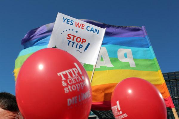 Yes we can: Stop TTIP. Plakat zwischen Regenbogenfahne und roten Luftballons. Großdemo Stop TTIP Berlin am 10.10.2015.  Foto: Helga Karl