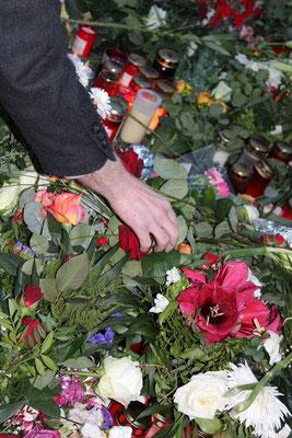 Arm eines Mannes - er legt Rote Rosen auf das Blumenmeer vor franz. Botschaft. Foto: Helga Karlot