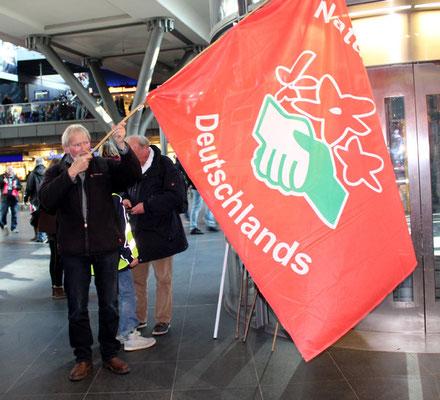 Mann mit großer Fahne Naturfreunde im Hauptbahnhof. Großdemo Stop TTIP Berlin am 10.10.2015.  Foto: Helga Karl