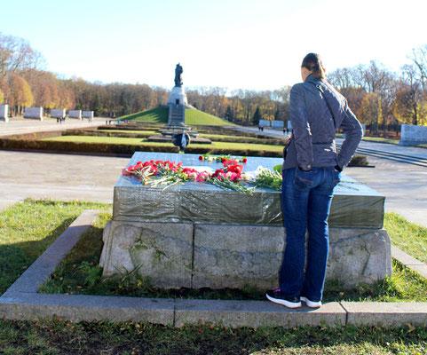 Ein Frau steht vor der durch Vandalismus zerstörten Steinplatte mit Blumen darauf, Blick auf das Denkmal Soldat mit Kind. Sowjetisches Ehrenmal Berlin. Foto: Helga Karl 8.11.2015